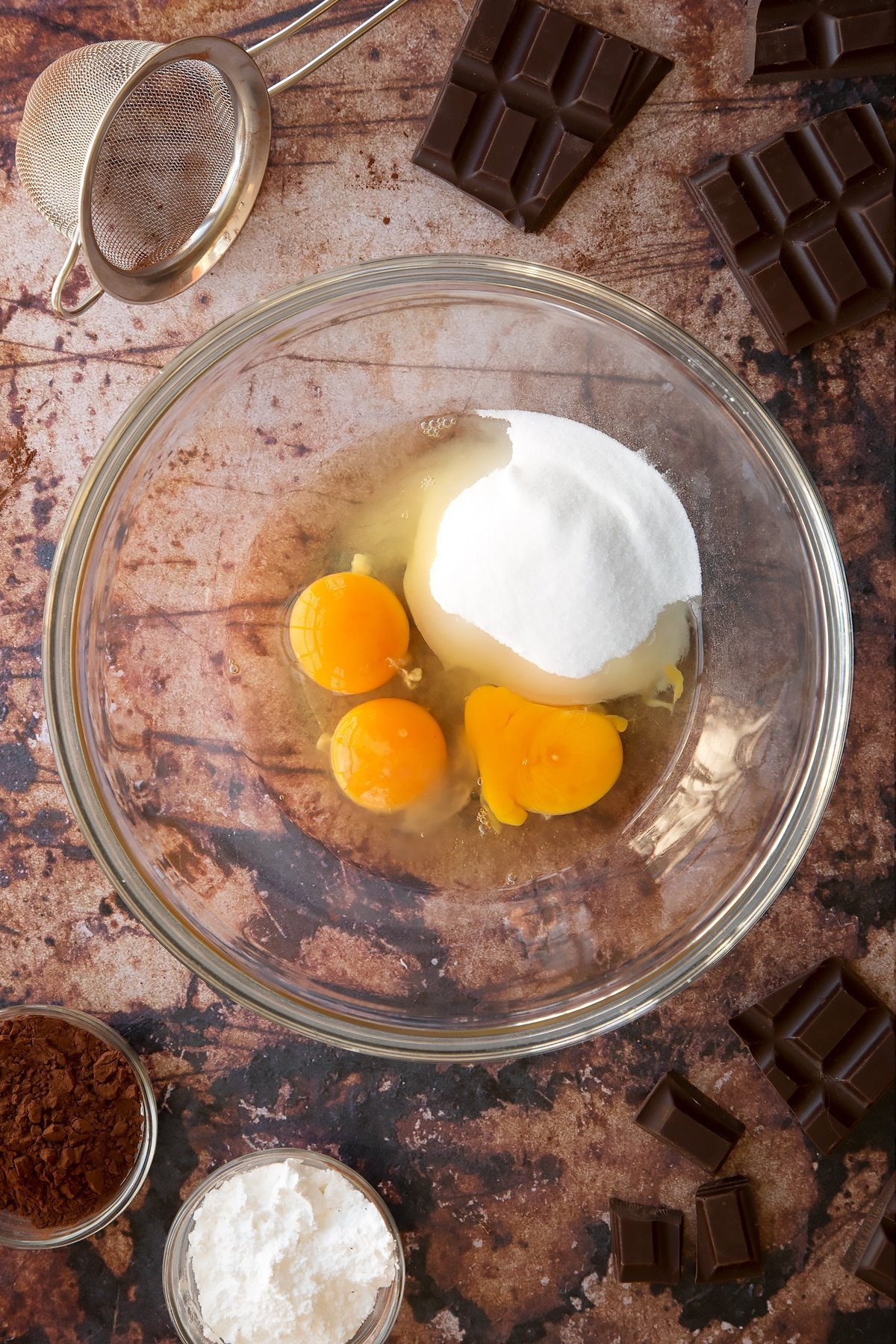 Eggs and caster sugar in a glass mixing bowl. Ingredients for the caterpillar cake recipe surround the bowl.