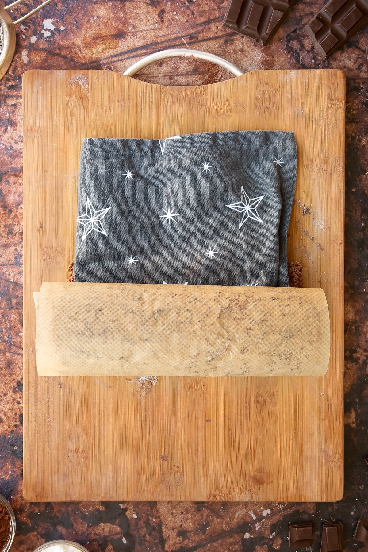 A chocolate sponge rolled with a tea towel on a wooden board and baking paper dusted with cocoa and icing sugar.