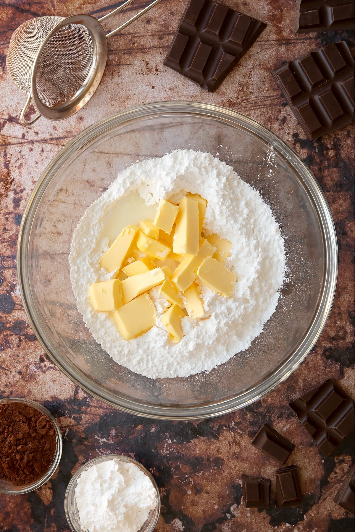 Butter, milk, vanilla and icing sugar in a glass mixing bowl. Ingredients for the caterpillar cake recipe surround the bowl.