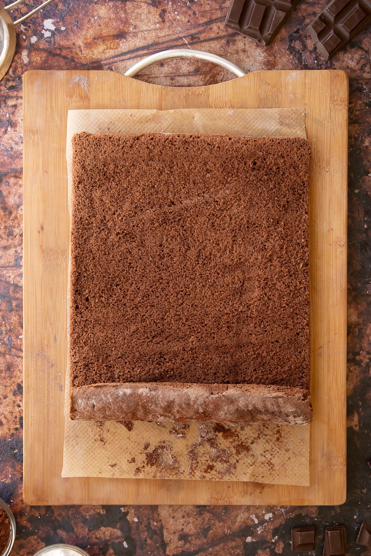 A chocolate sponge unrolled on a wooden board and baking paper dusted with cocoa and icing sugar.