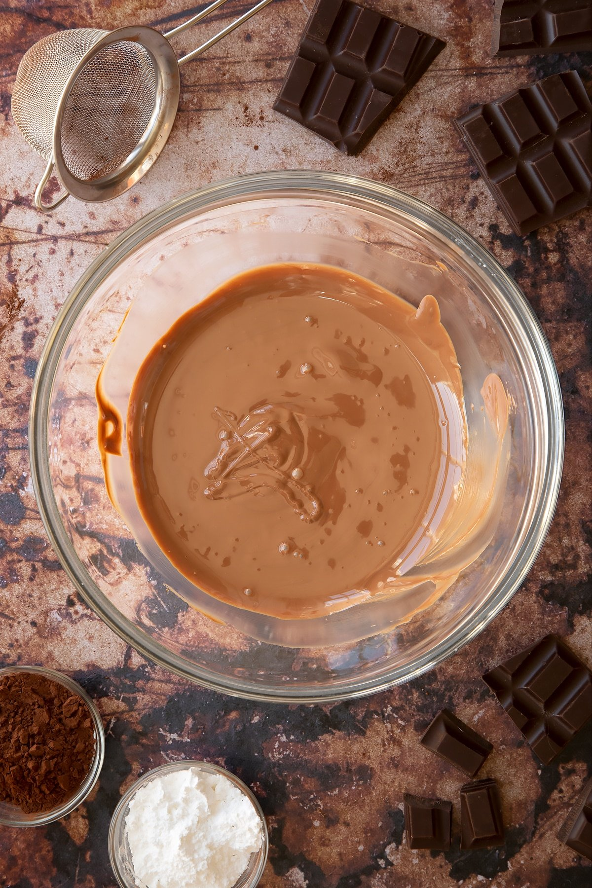 Melted chocolate in a glass mixing bowl. Ingredients for the caterpillar cake recipe surround the bowl.