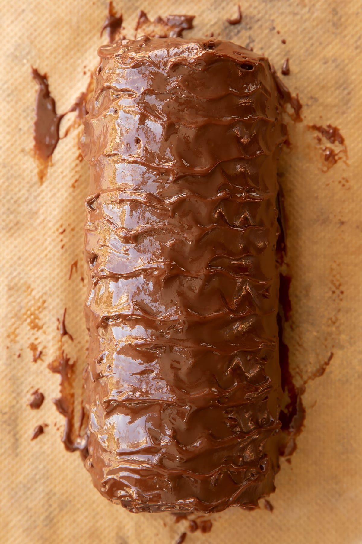 Chocolate Swiss roll covered with chocolate ganache on baking paper.