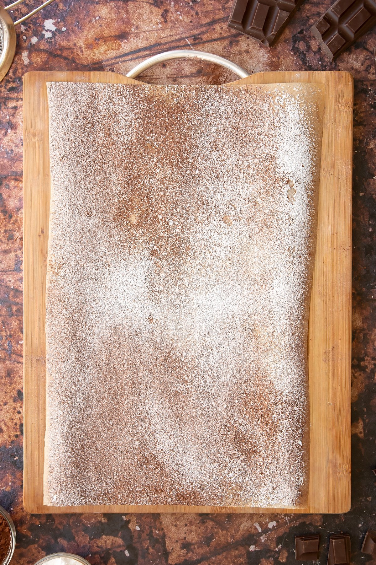 A wooden board and baking paper dusted with cocoa and icing sugar.