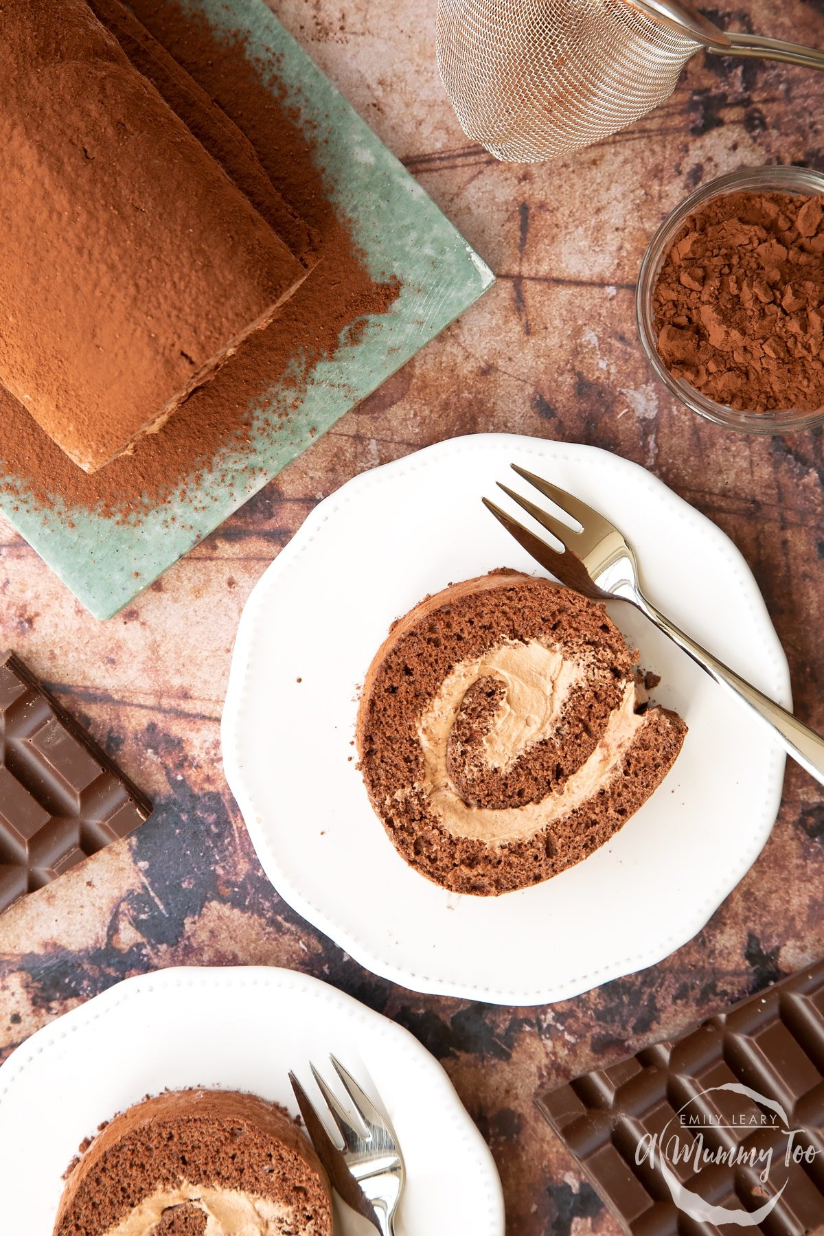 Two slices of Chocolate Swiss roll on white plates with forks, shown from above.