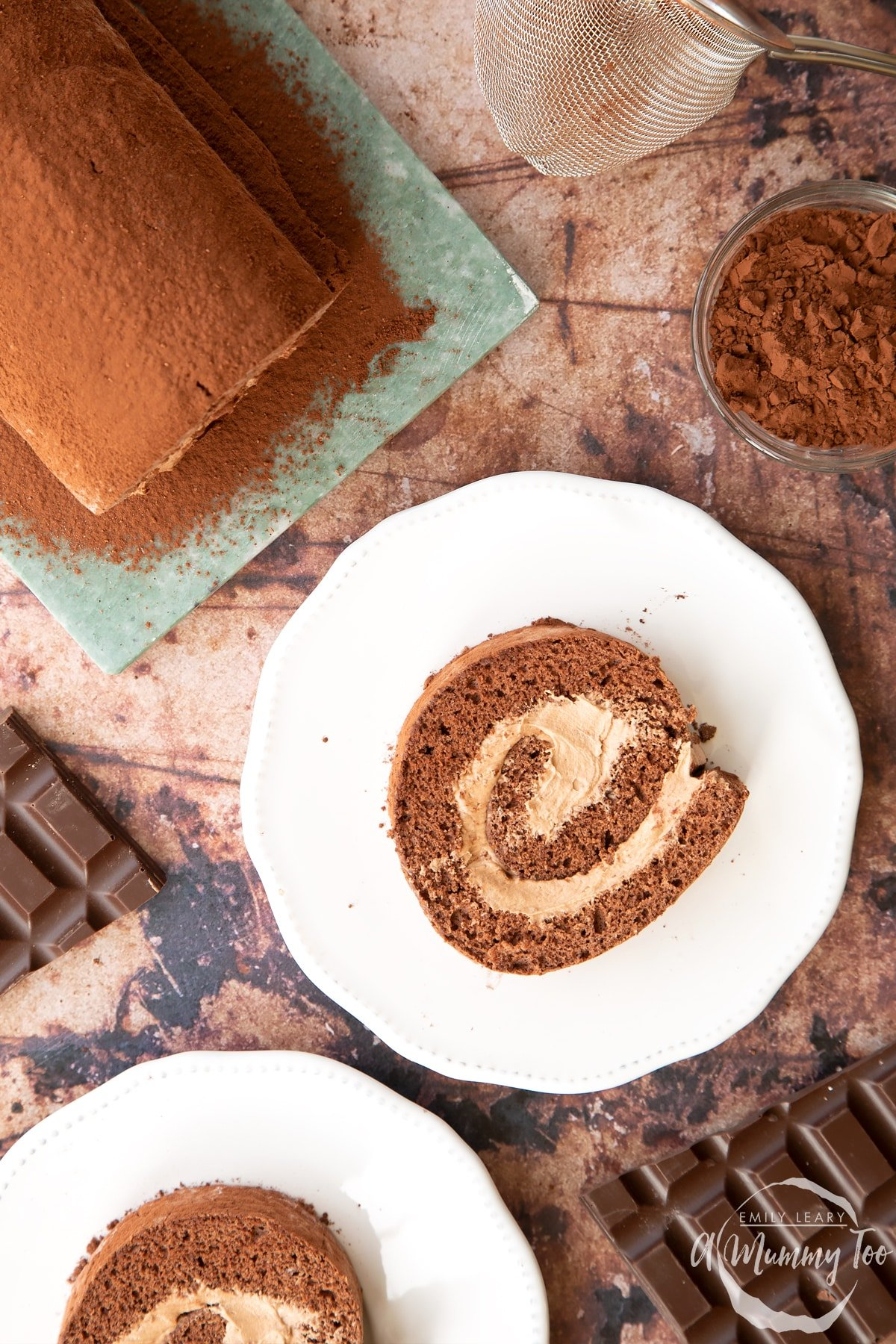 Two slices of Chocolate Swiss roll on white plates, shown from above.