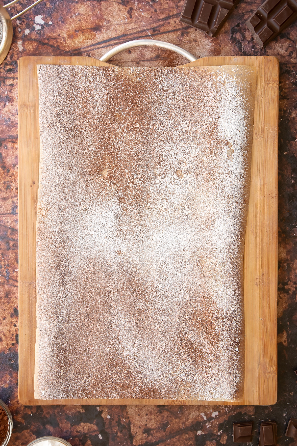 Wooden board topped with a piece of baking paper, dusted with cocoa and icing sugar.