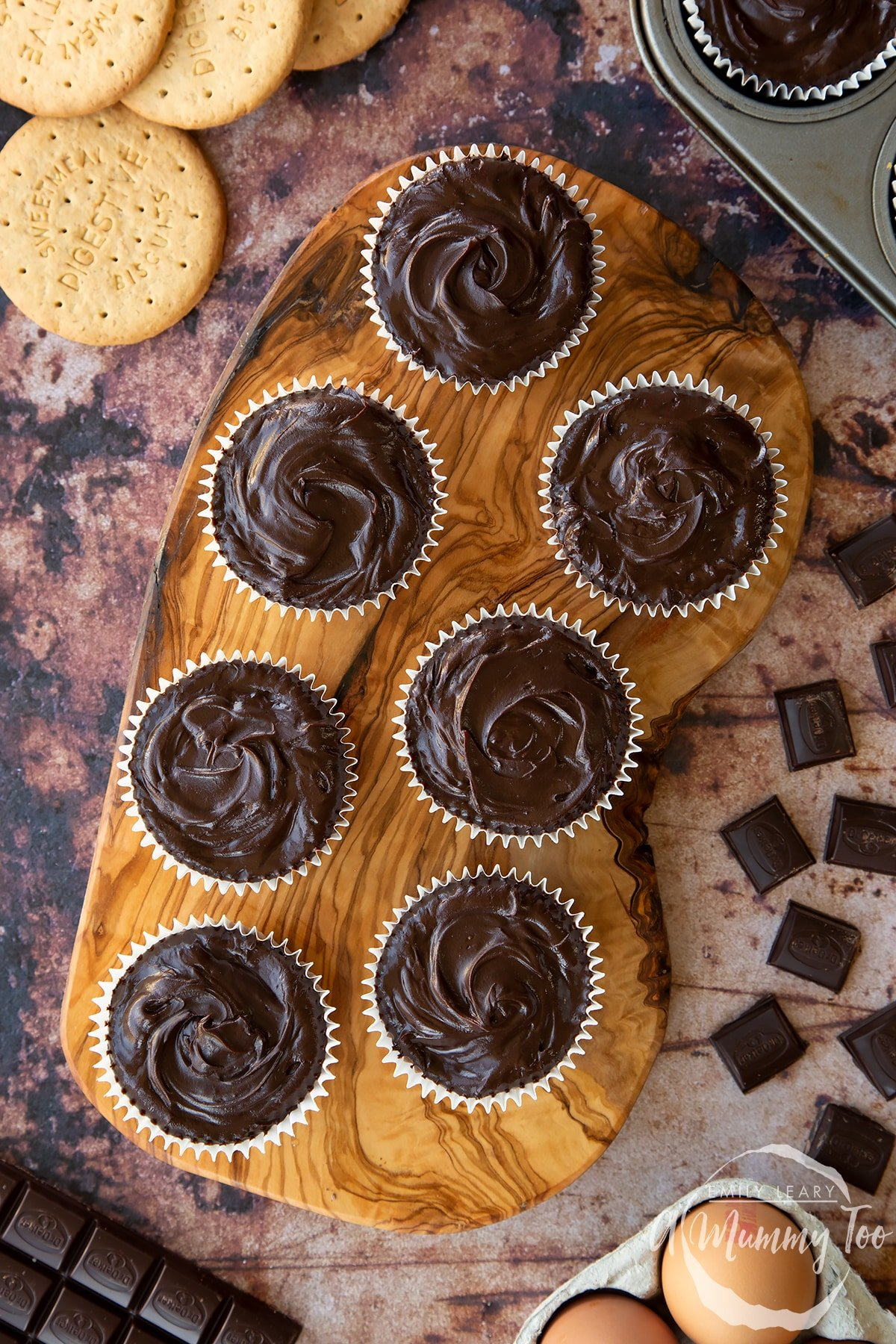 Chocolate cheesecake cupcakes in rows on an olive wood board, shown from above.