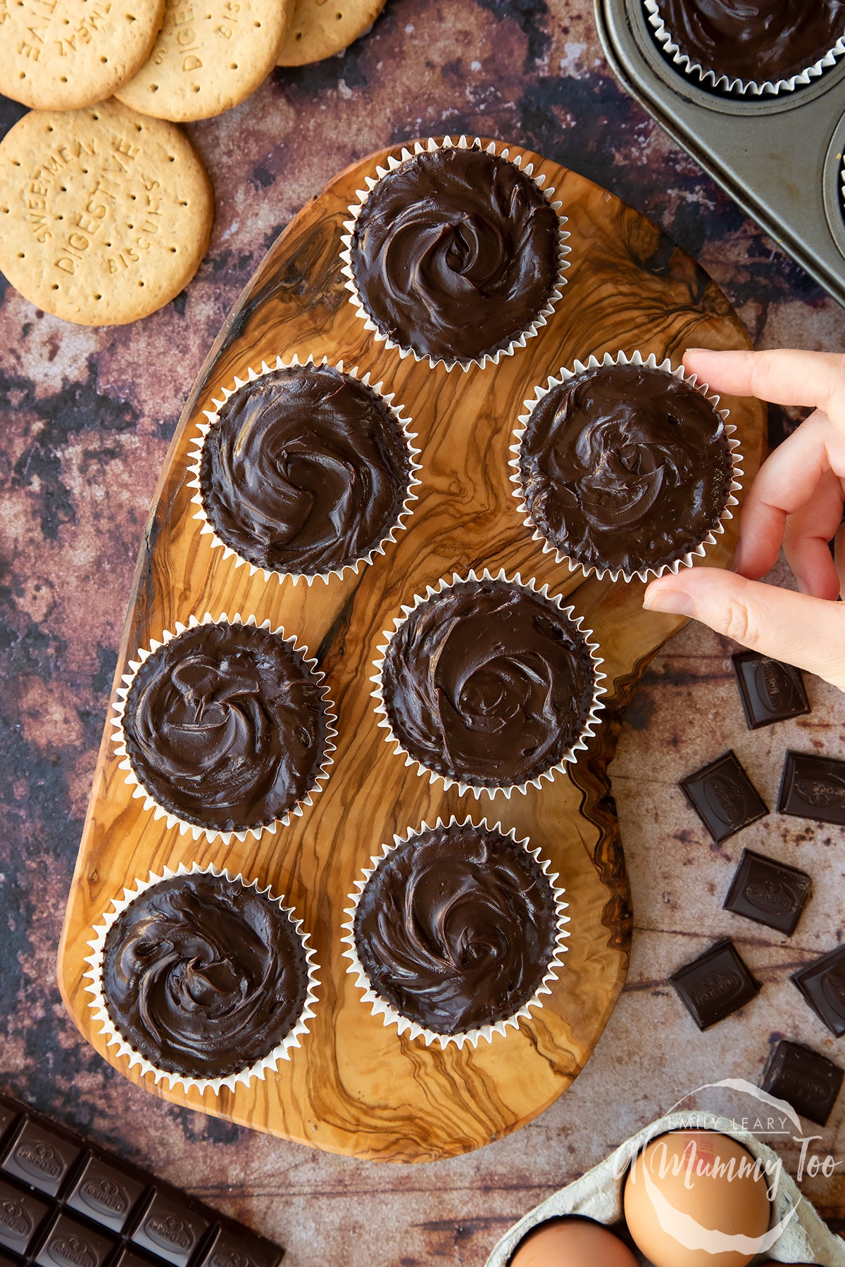 Chocolate cheesecake cupcakes in rows on an olive wood board, shown from above. A hand reaches for one.