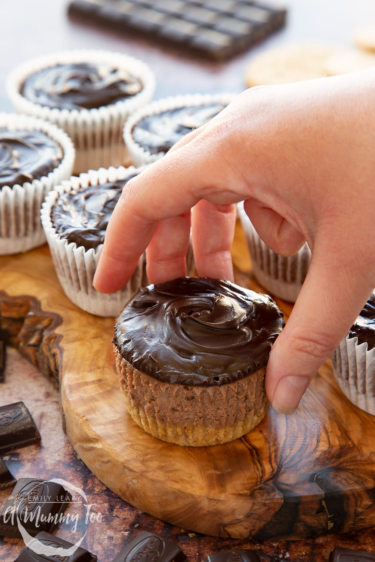 Chocolate cheesecake cupcakes in rows on an olive wood board. The one in the foreground has been unwrapped and a hand reaches for it.