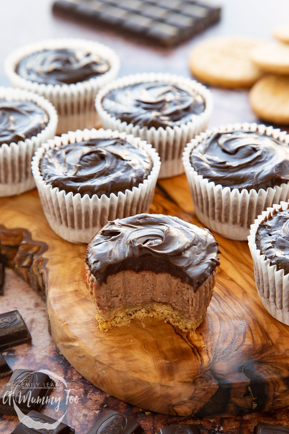 Chocolate cheesecake cupcakes in rows on an olive wood board. The one in the foreground has been unwrapped and has a bite out of it.