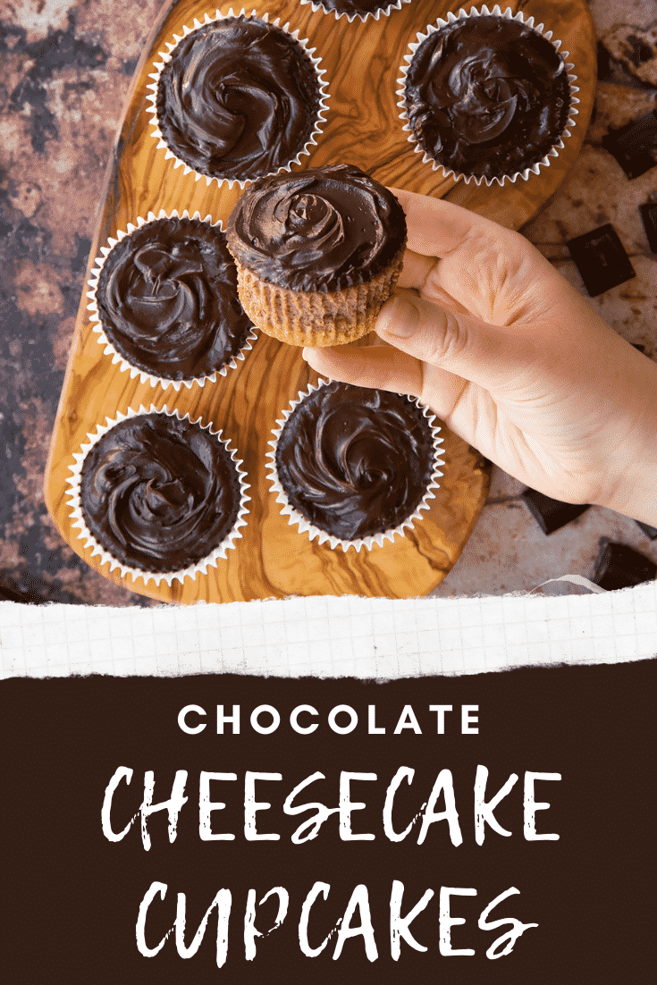 Chocolate cheesecake cupcakes in rows on an olive wood board from above. A hand holds one. Caption reads: chocolate cheesecake cupcakes