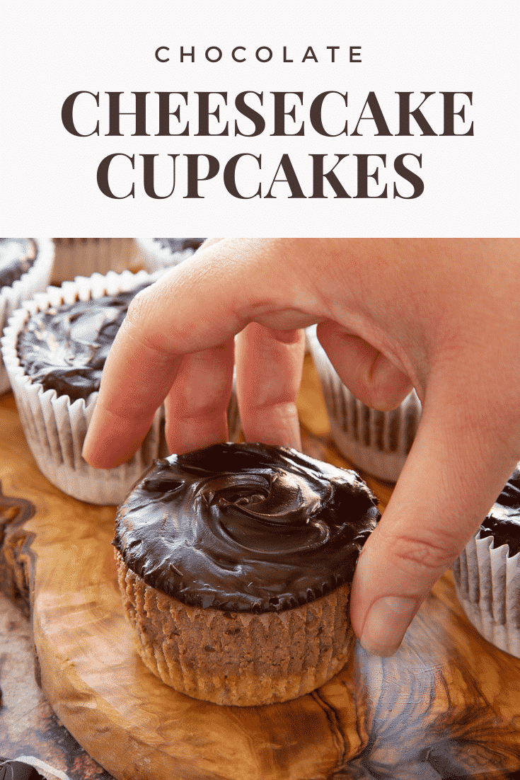 Chocolate cheesecake cupcakes in rows on an olive wood board. A hand reaches for one. Caption reads: Chocolate cheesecake cupcakes