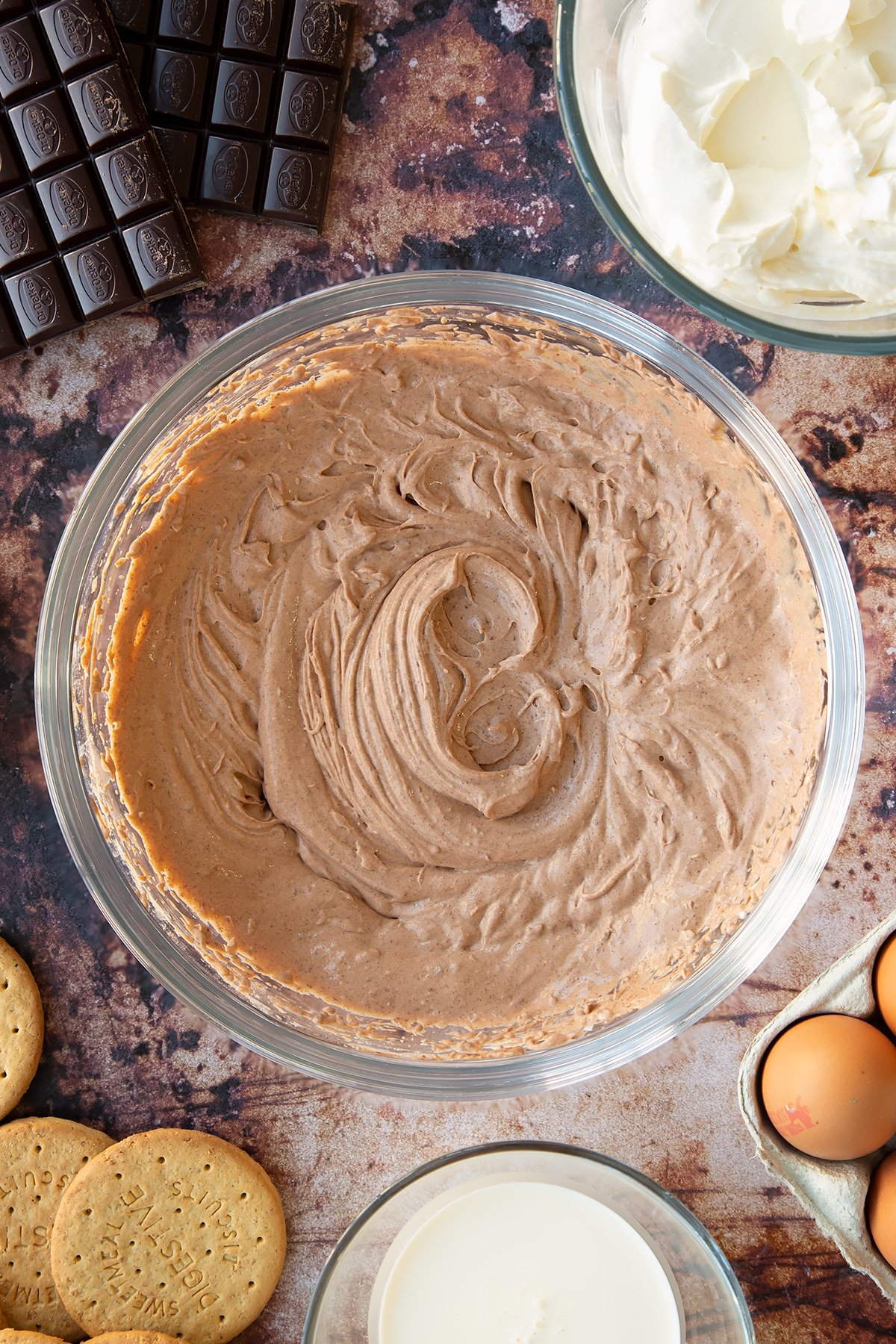 Chocolate cheesecake mix in a glass bowl. Ingredients to make chocolate cheesecake cupcakes surround the bowl.
