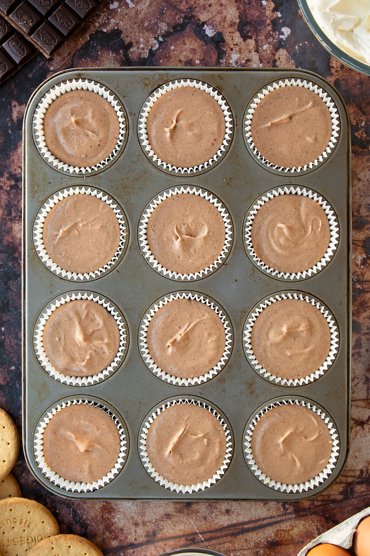 Chocolate cheesecake mix in cupcake cases in a muffin tray. Ingredients to make chocolate cheesecake cupcakes surround the tray.