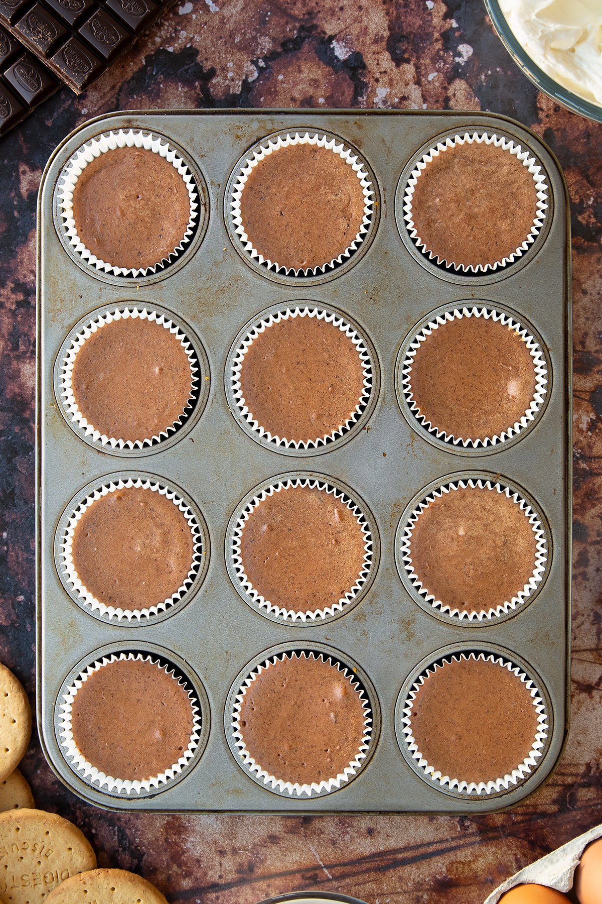 Chocolate cheesecake cupcakes, freshly baked in a muffin tray.