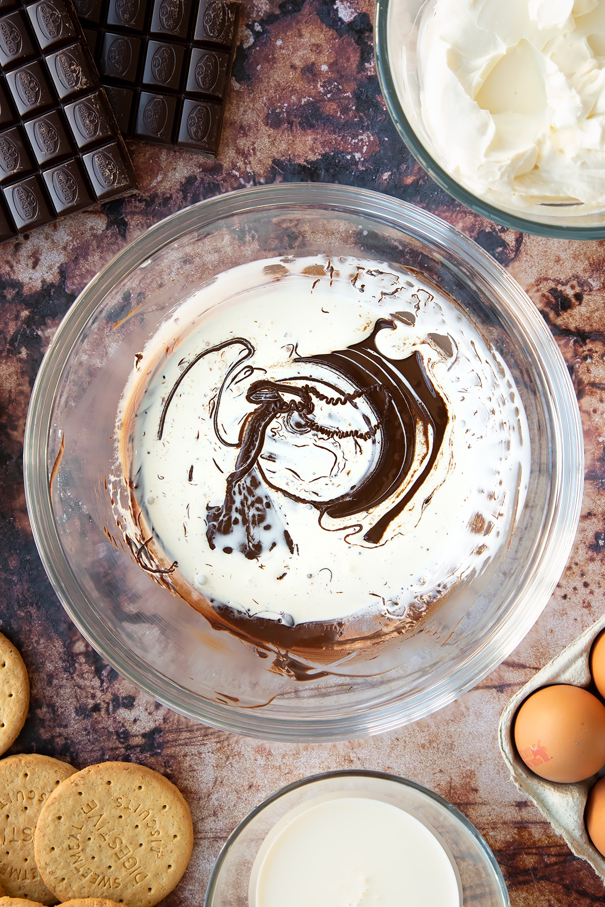Melted dark chocolate and double cream in a glass bowl. Ingredients to make chocolate cheesecake cupcakes surround the bowl.