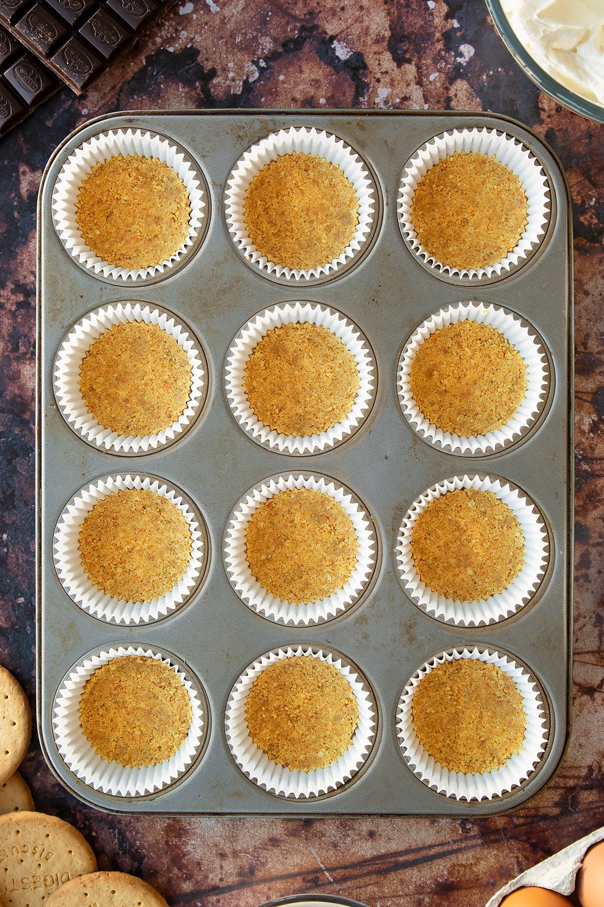 Crushed digestive biscuits mixed with melted butter pressed into cupcake cases in a muffin tray. Ingredients to make chocolate cheesecake cupcakes surround the tray.