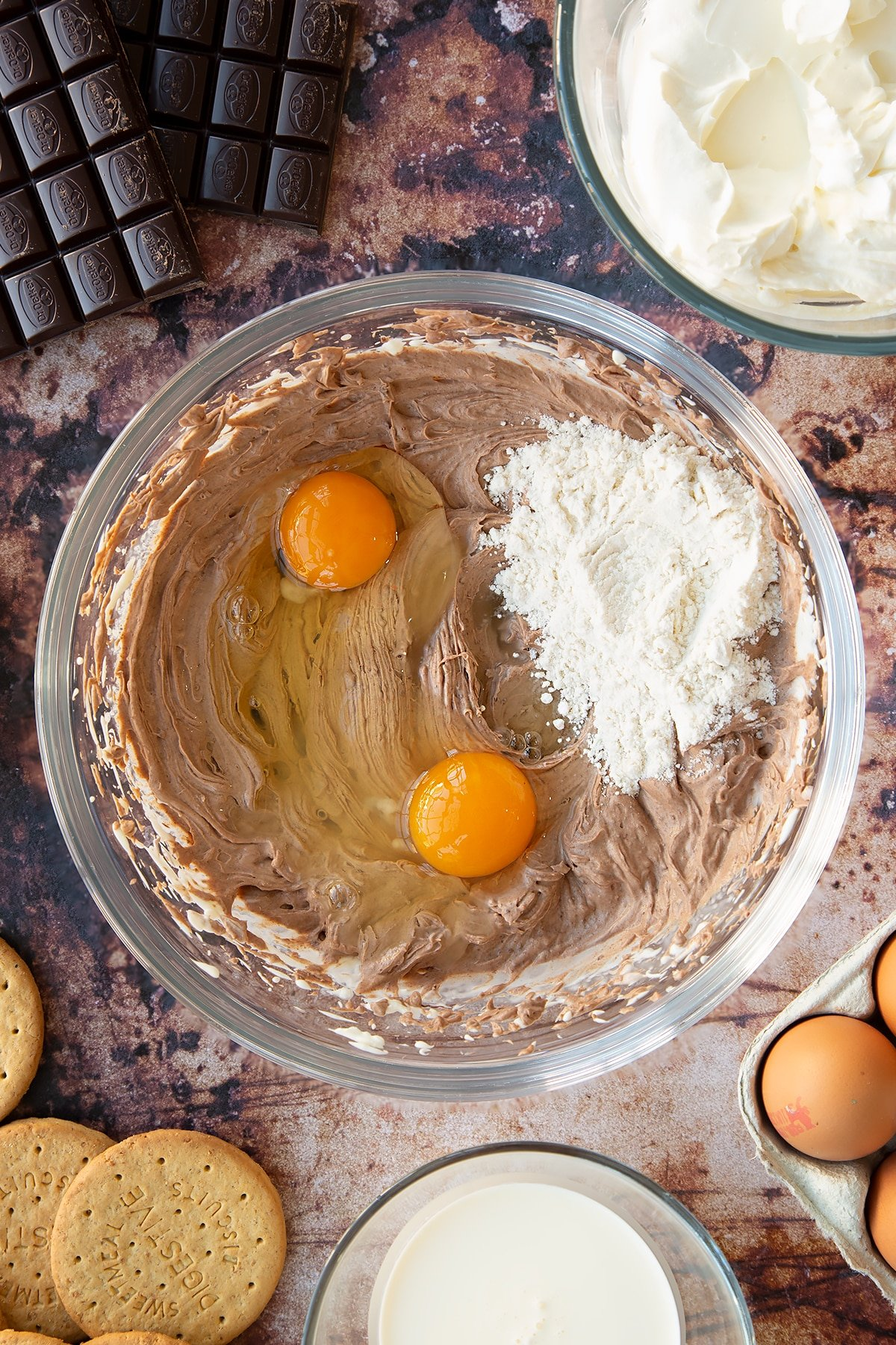 Cream cheese, sugar, cream and melted dark chocolate whisked together in a glass bowl with eggs and flour on top. Ingredients to make chocolate cheesecake cupcakes surround the bowl.