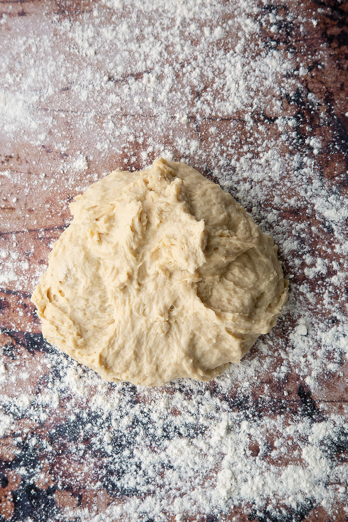 Overhead shot of sticky white dough on a floured surface