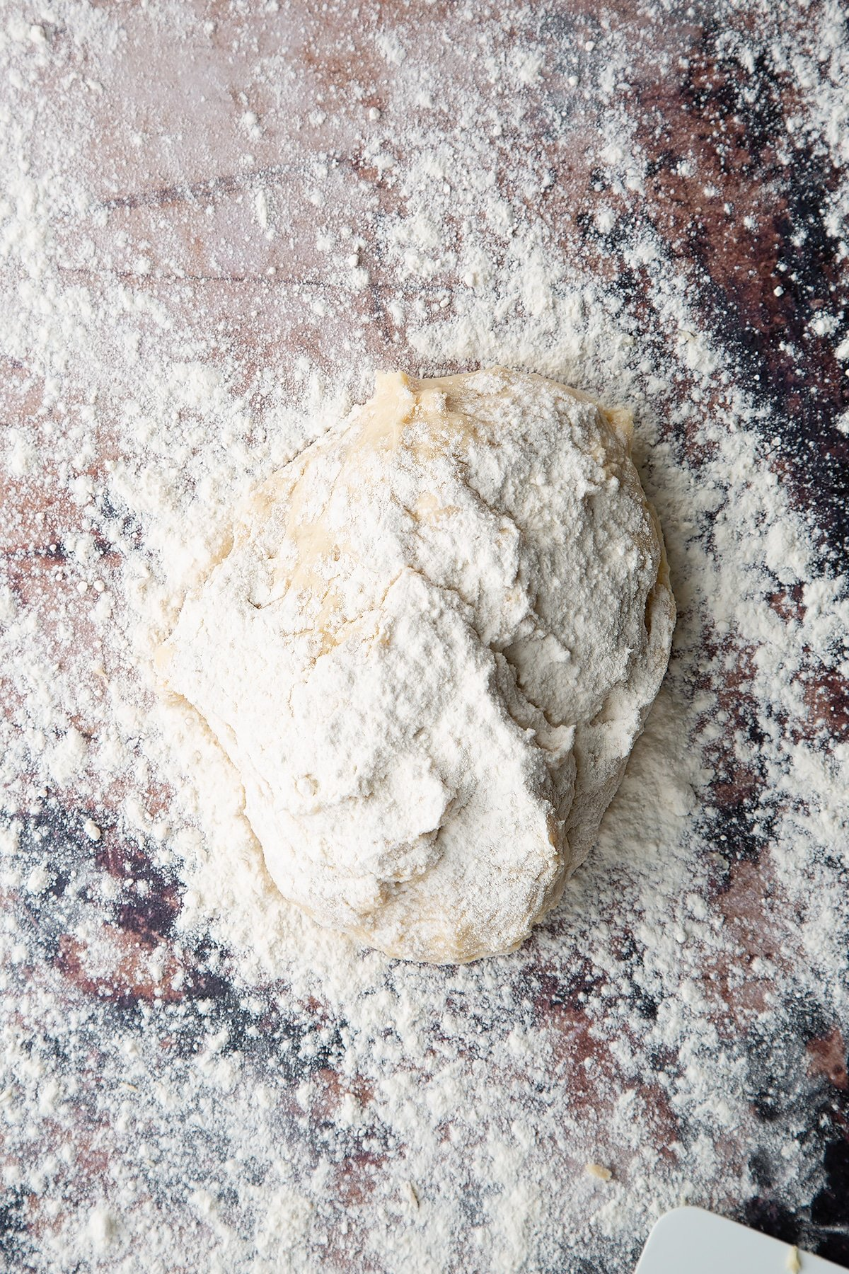 Overhead shot of white dough on a floured surface covered in flour