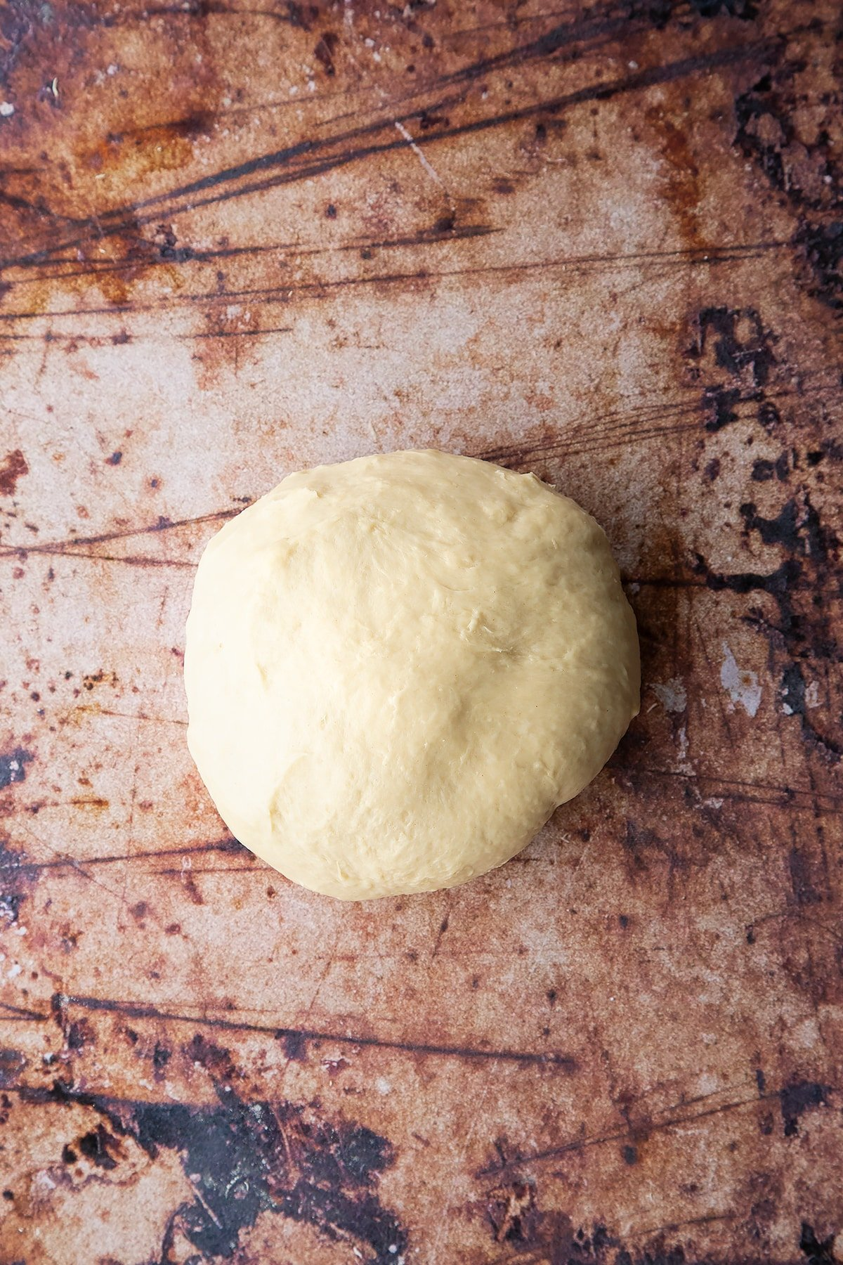 Overhead shot of white dough ball formed on a clean surface