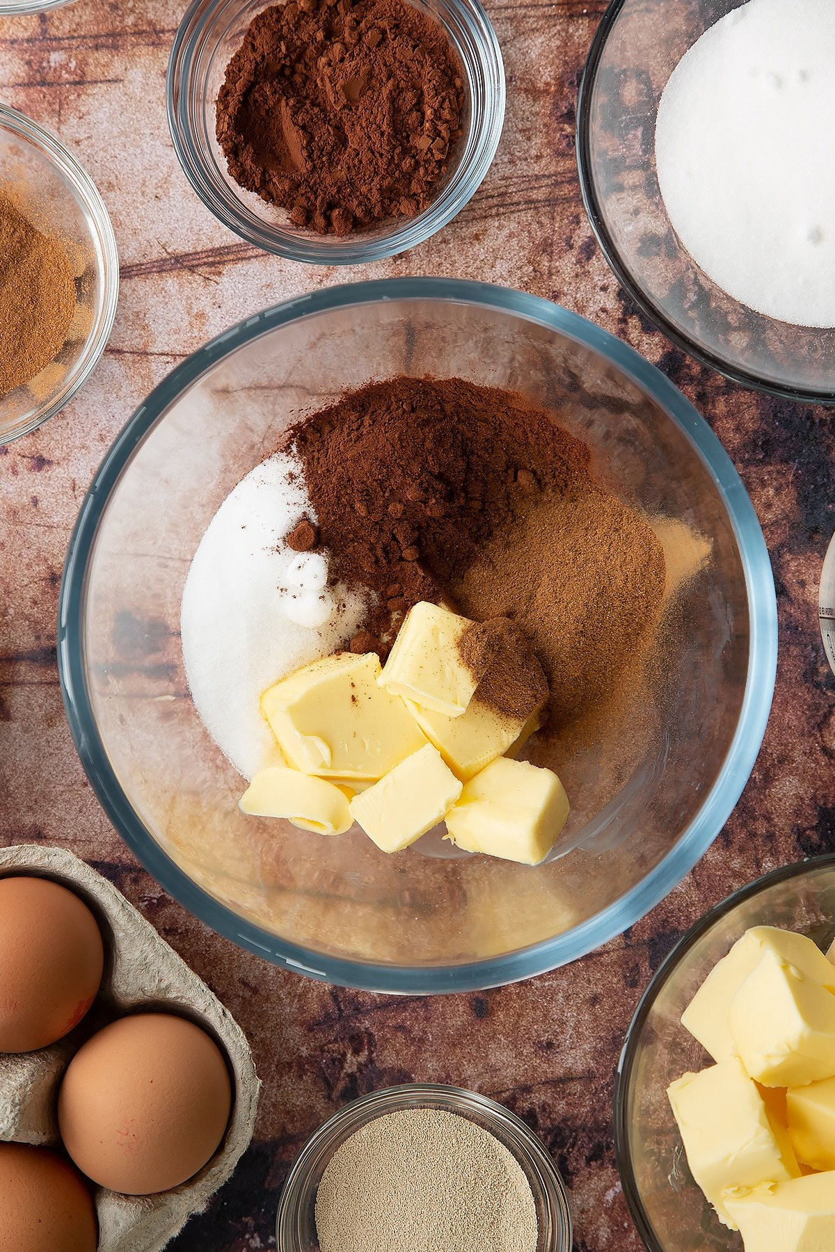Over head shot of cinnamon, sugar, butter and cocoa in a large clear bowl