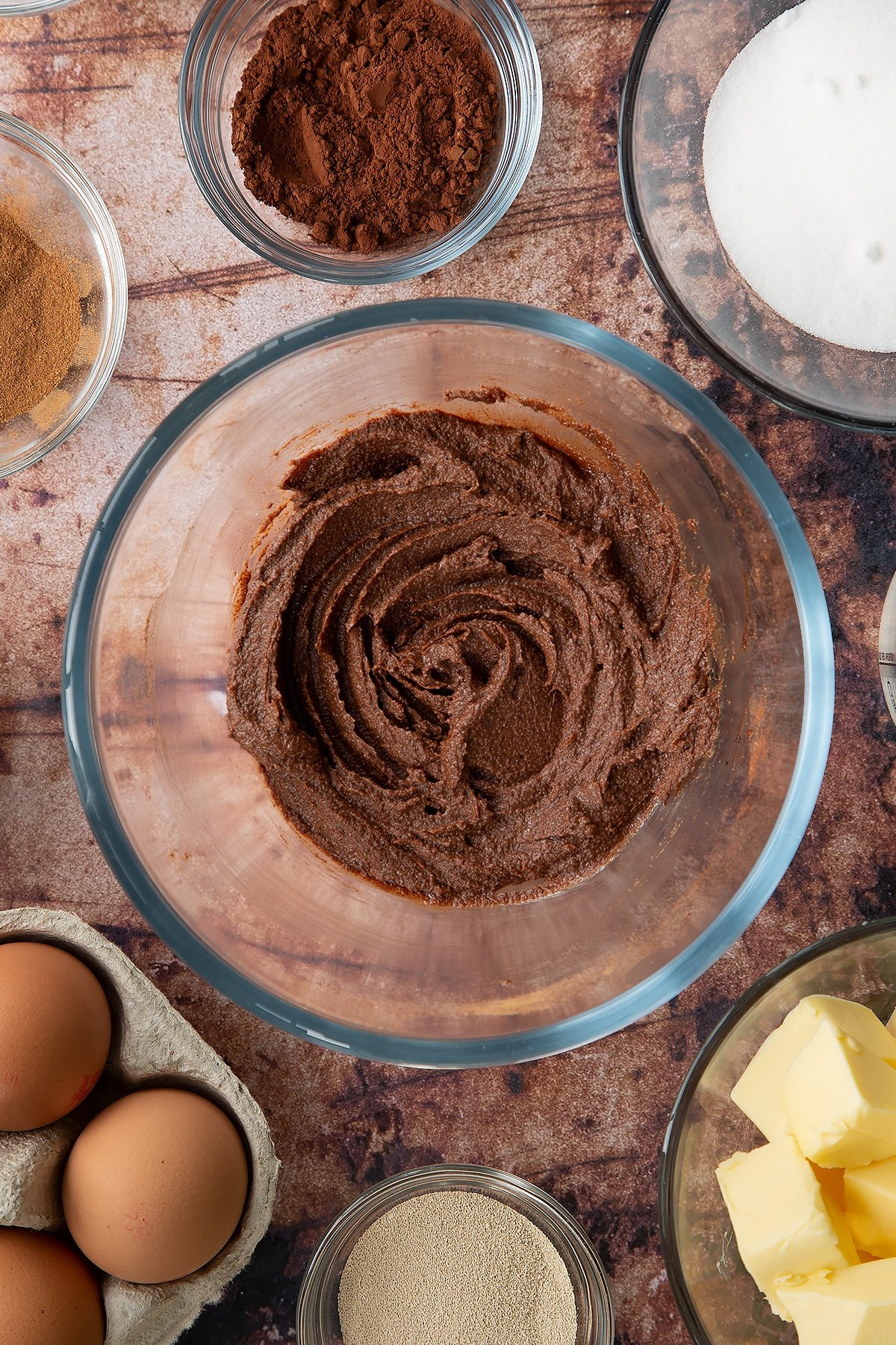 Overhead shot of butter, sugar, cinnamon and cocoa mixed together in a large clear bowl