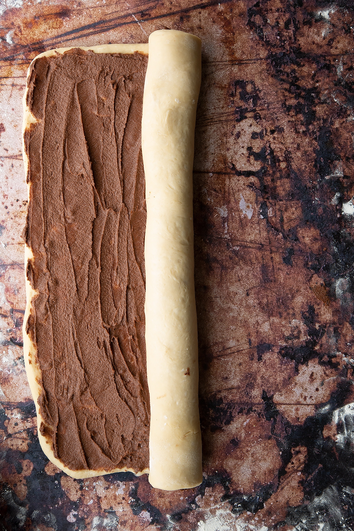 Overhead shot of dough layered with chocolate spread and rolled on one side.