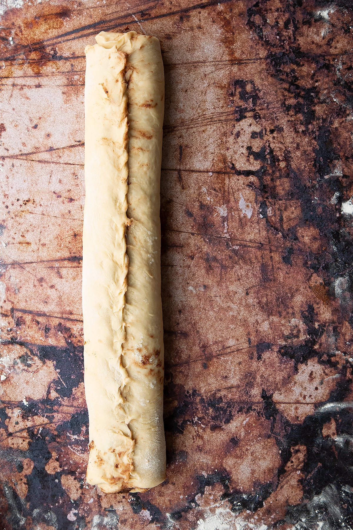 Overhead shot of dough layered with chocolate spread and rolled up into a sausage shape