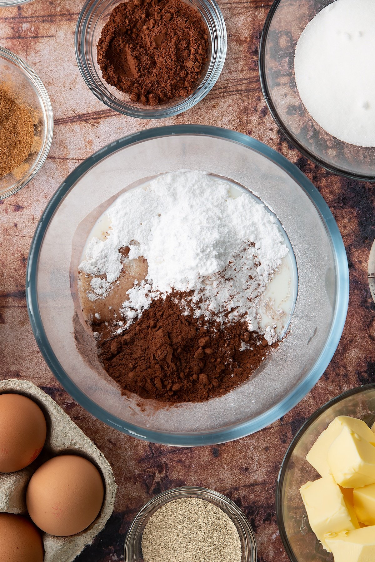 Overhead shot of icing sugar, milk and cocoa in a large clear bowl