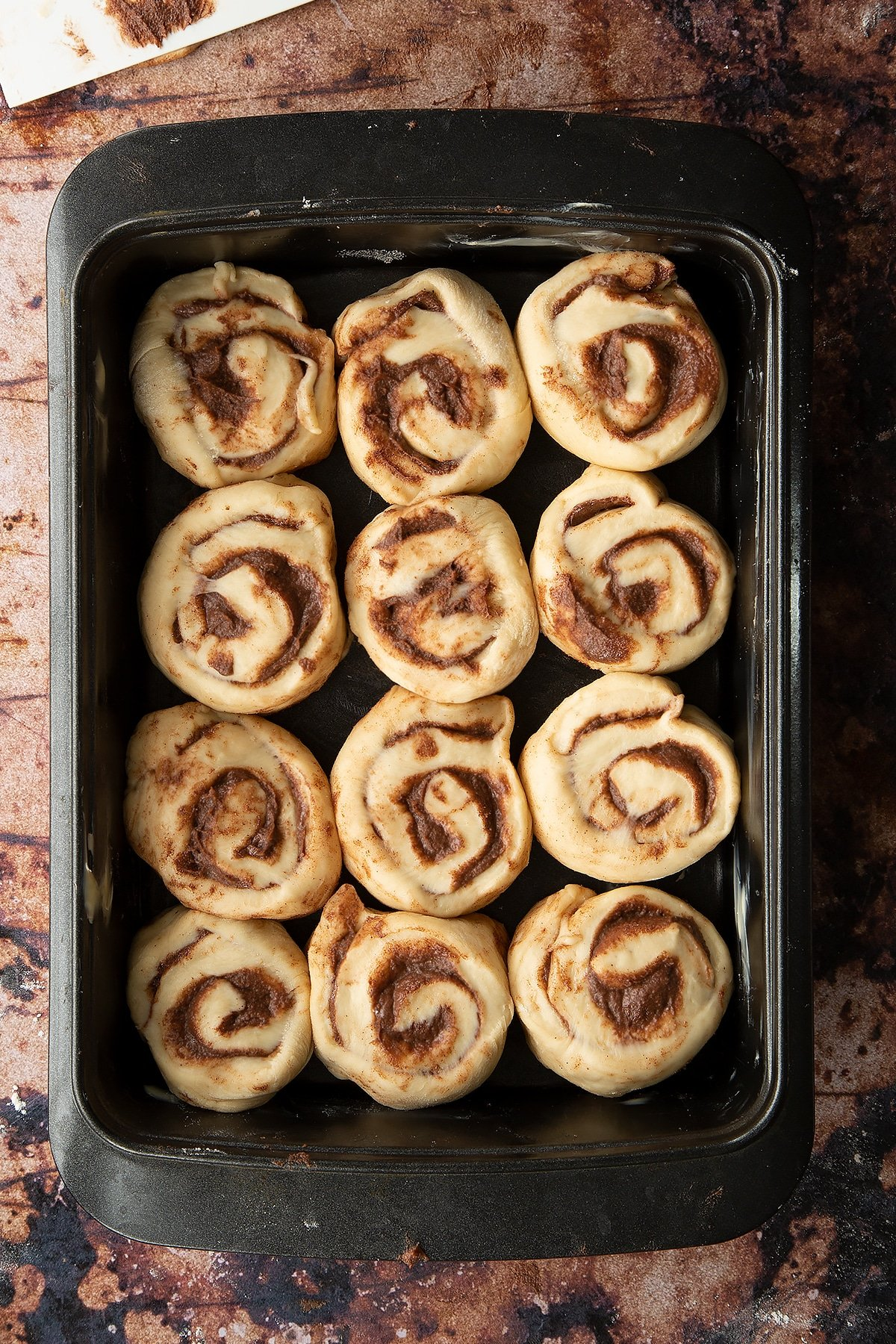 Overhead shot of dough rolled up into sections laid out in a deep baking tray