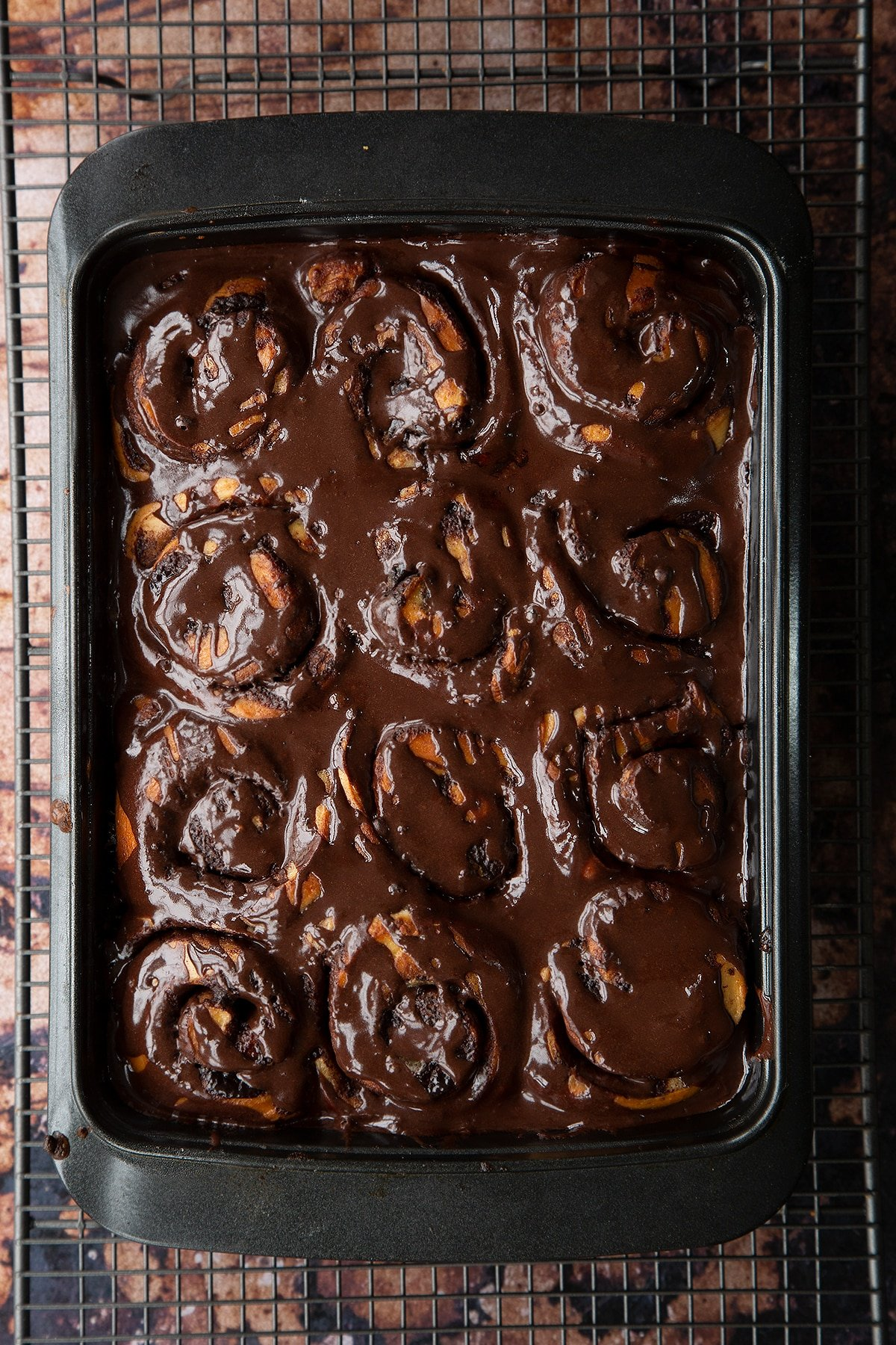 Overhead shot of chocolate cinnamon buns baked in a baking tray covered in chocolate sauce