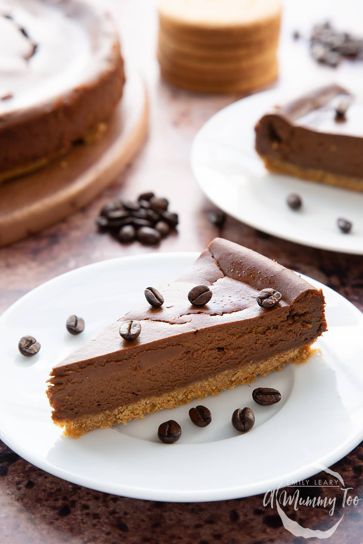 Front view shot of a piece of coffee cheesecake topped with coffee beans on a white plate with the A Mummy Too logo in the corner