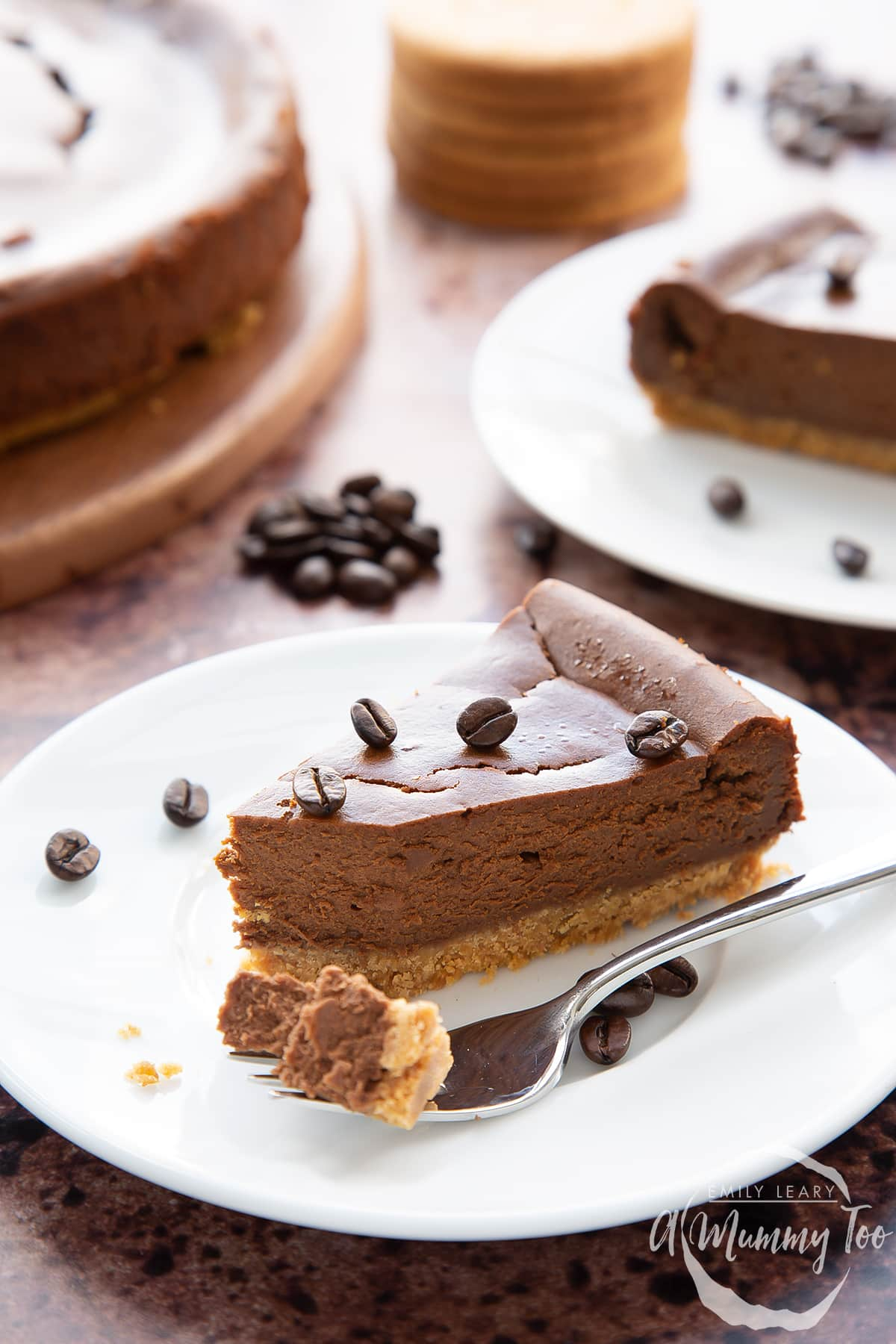 Front view shot of a piece of coffee cheesecake topped with coffee beans on a white plate with a fork with the tip of the cheesecake with the A Mummy Too logo in the corner