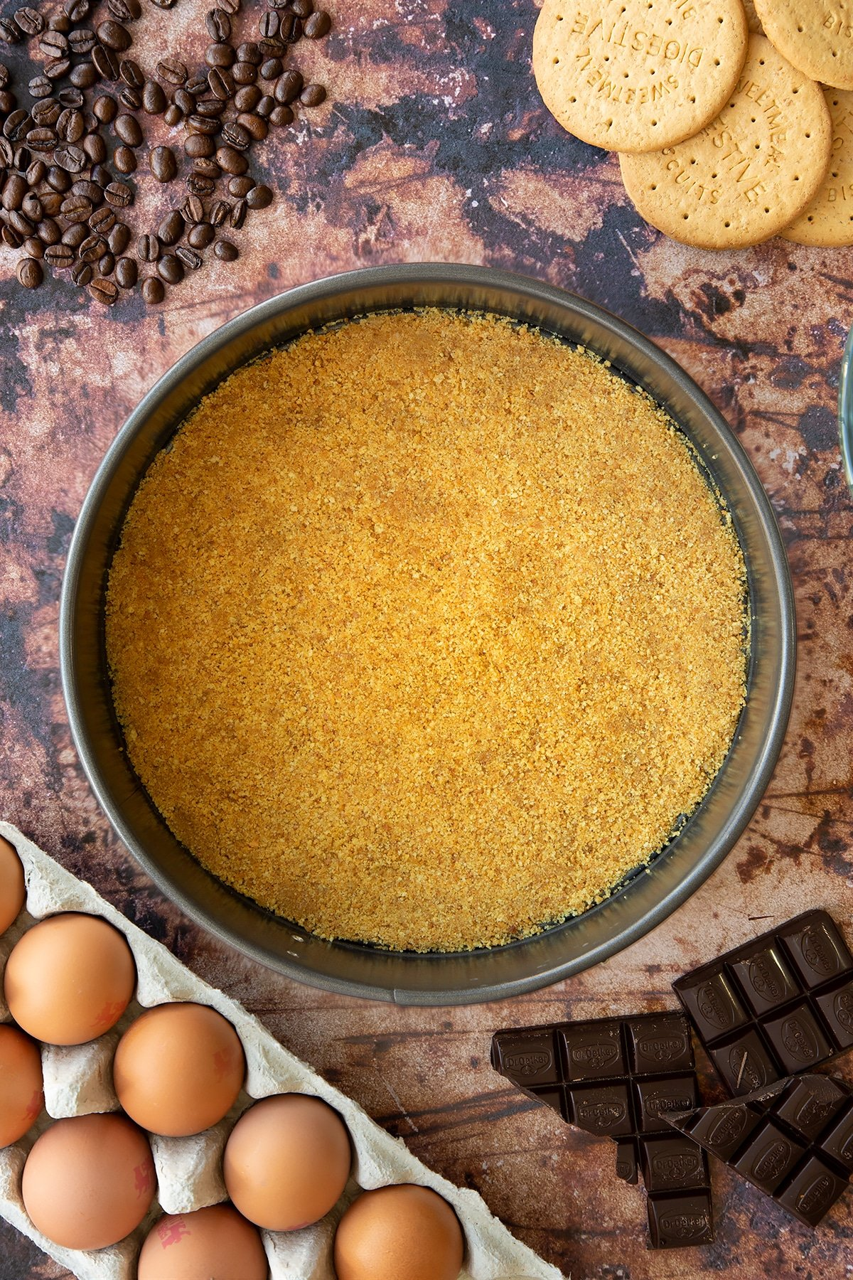 Overhead shot of butter and biscuit crumb mix pressed down flat in a large metal cake tin