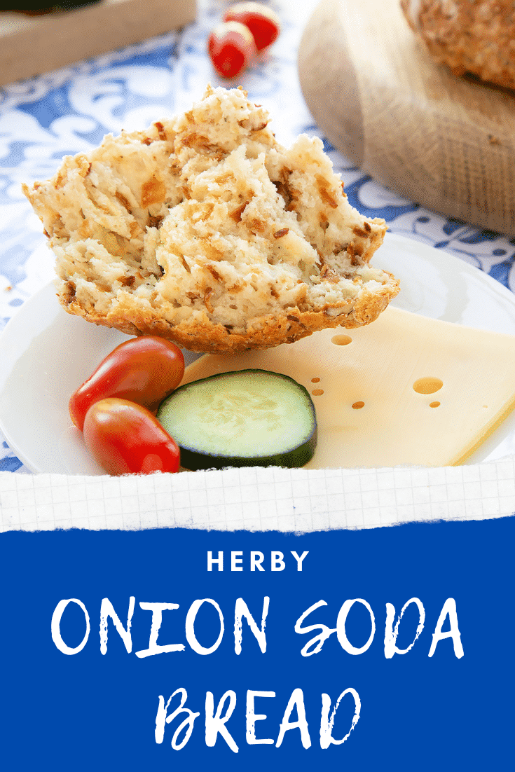 Onion soda bread on a white plate with cheese and salad. A hand holds a piece. Caption reads: herby onion soda bread