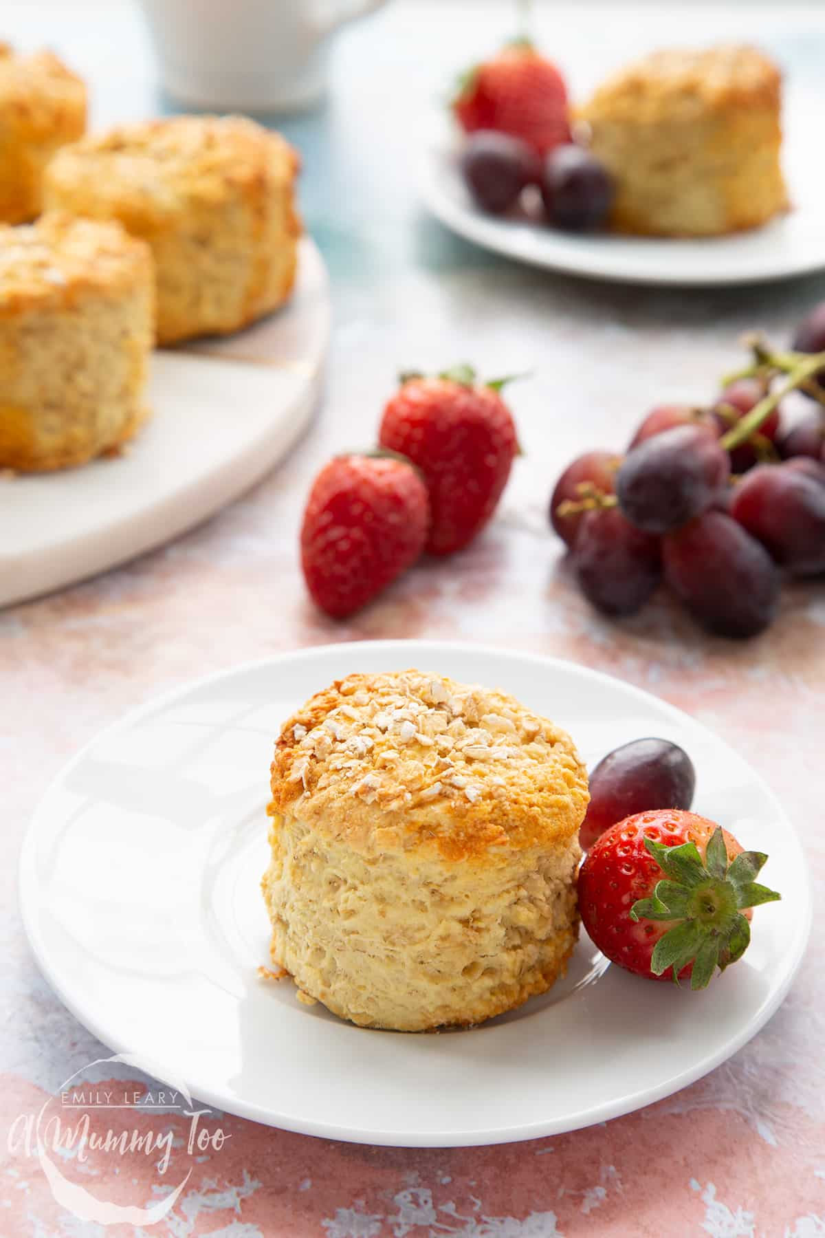 An oatmeal scone on a white plate with some fruit. More oatmeal scones sit on a board in the background.