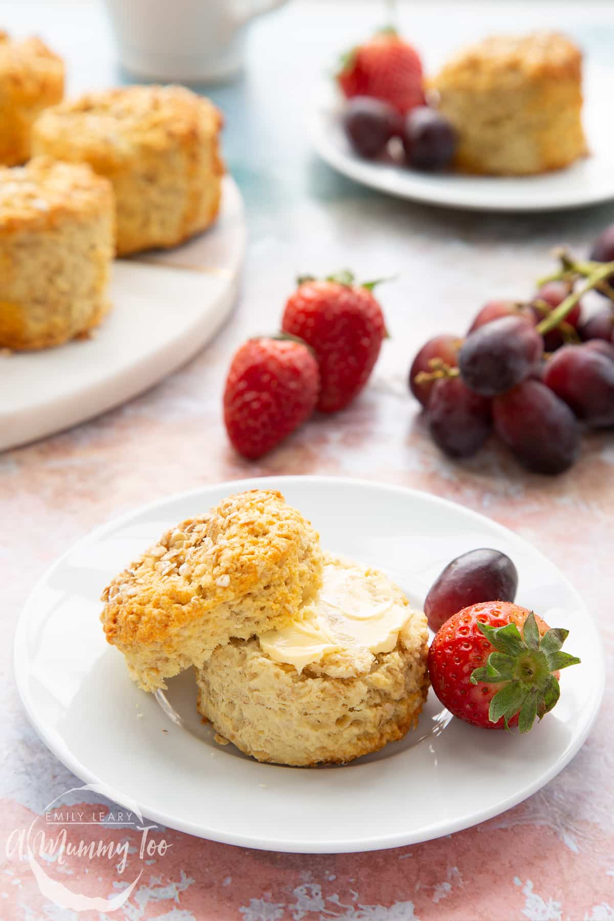 An oatmeal scone on a white plate with some fruit. The scone has been split and buttered. More oatmeal scones sit on a board in the background.