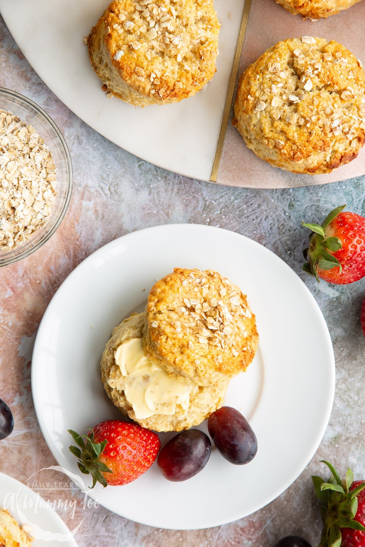 An oatmeal scone on a white plate with some fruit. The scone has been split and buttered. Shown from above.