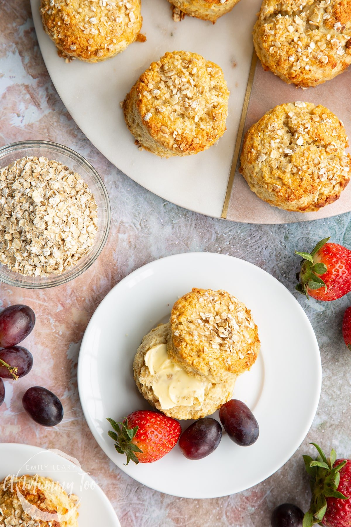 An oatmeal scone on a white plate with some fruit. Shown from above. There are more scones on a board to the edge of the frame.