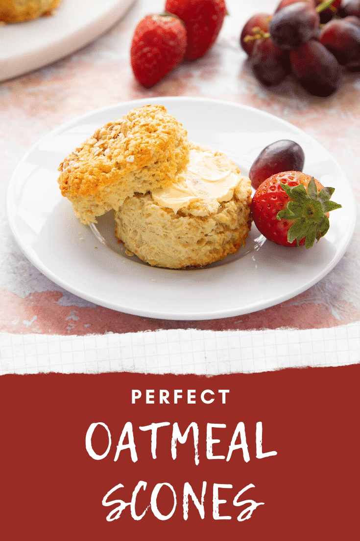 Oatmeal scone on a white plate. It has been split and buttered. Caption reads: Perfect Oatmeal Scones