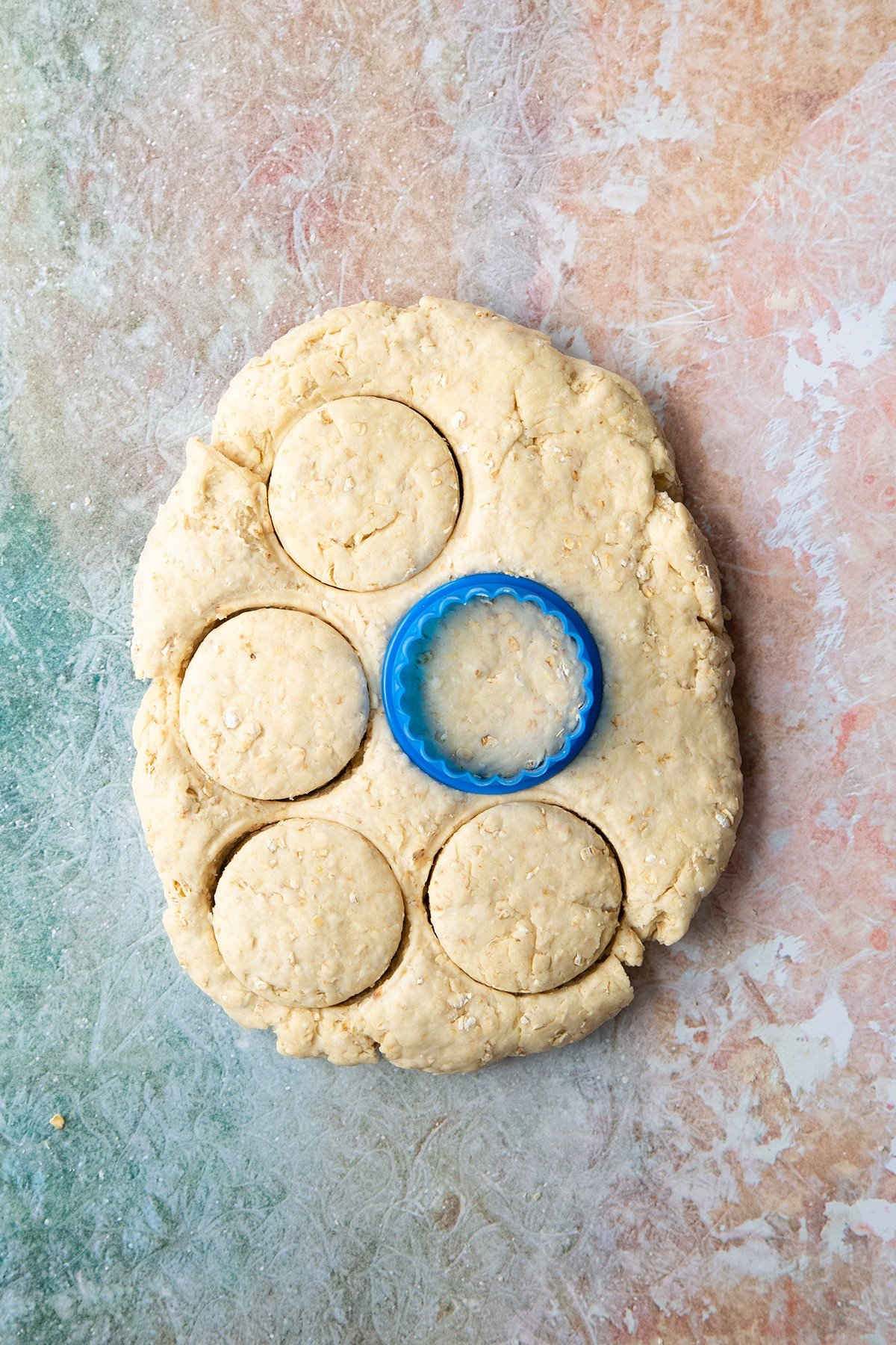 Oatmeal scone dough pressed to a thick slab. Some rounds have been cut out using a blue cookie cutter.