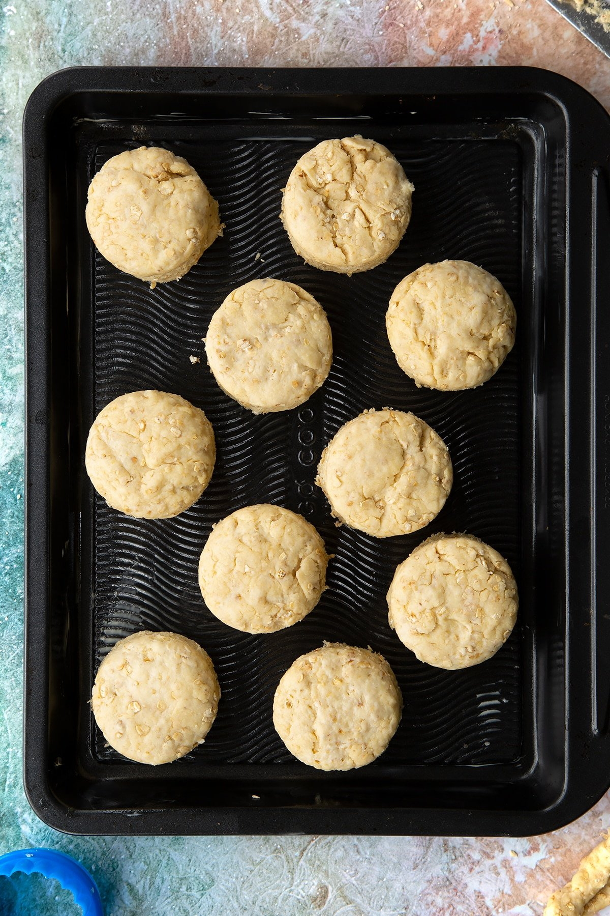 Oatmeal scone rounds of dough on a baking tray.