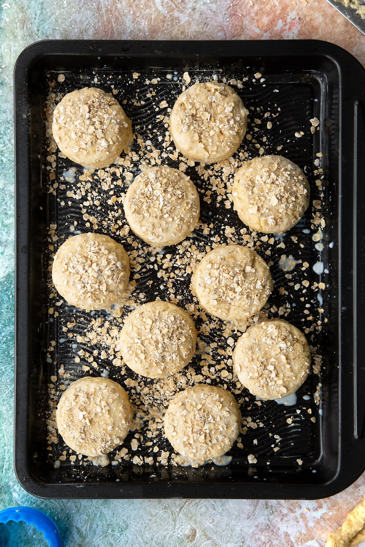 Oatmeal scone rounds of dough, brushed with milk and scattered with oats on a baking tray.
