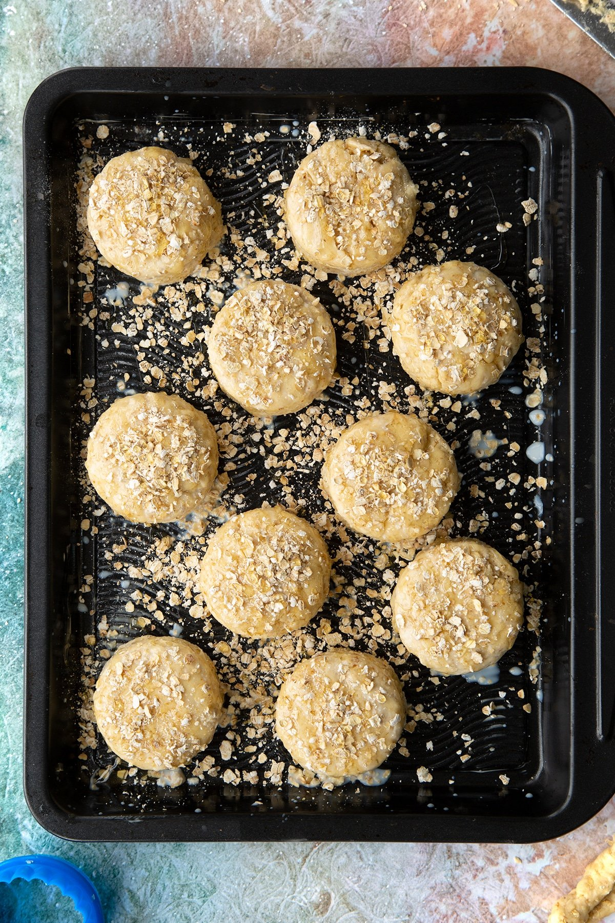 Oatmeal scone rounds of dough, brushed with milk, scattered with oats and drizzled with honey on a baking tray.