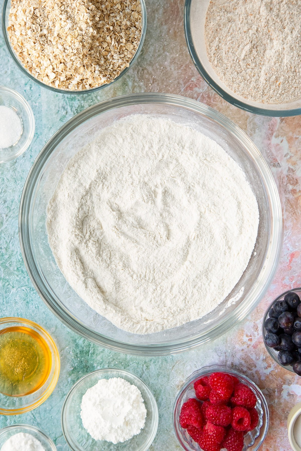 Self-raising flour, bicarbonate of soda and sugar combined in a glass mixing bowl. Ingredients to make oatmeal scones surround the bowl.