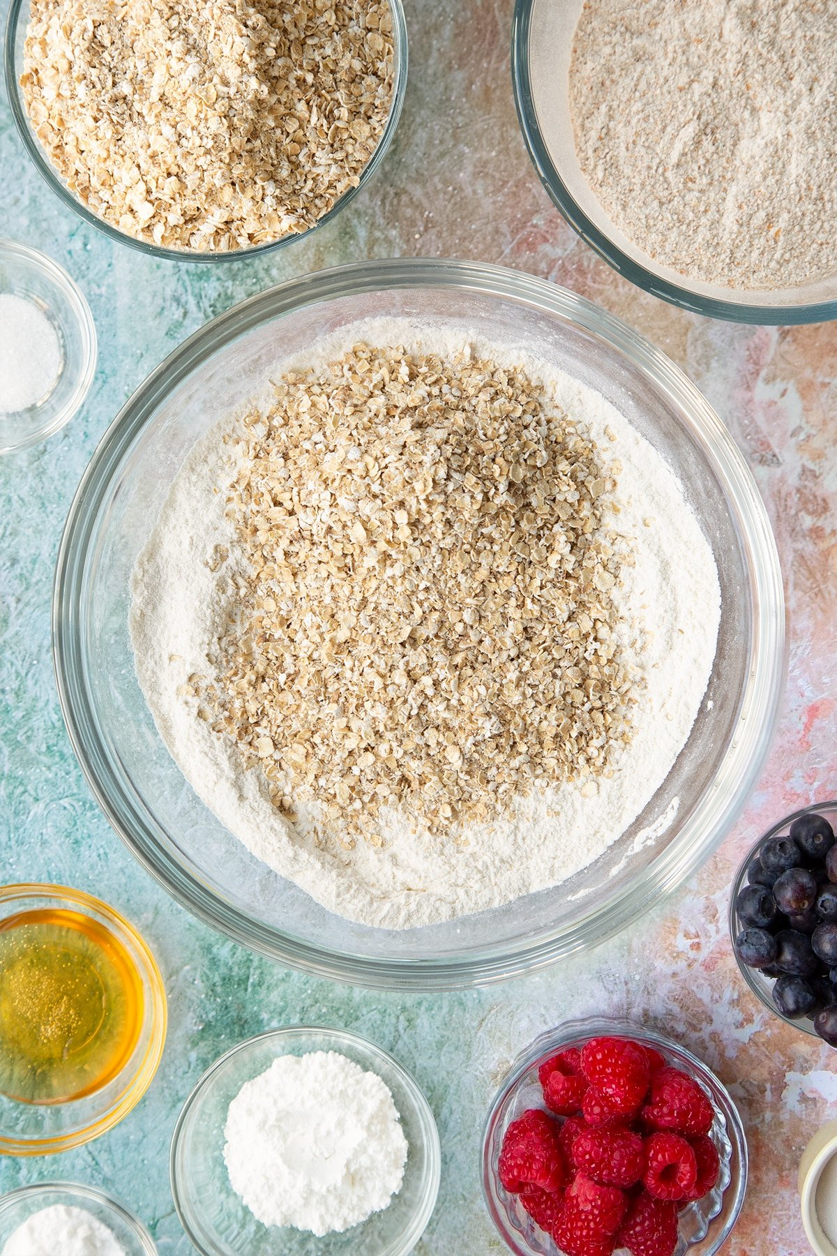 Self-raising flour, bicarbonate of soda and sugar combined in a glass mixing bowl with oats on top. Ingredients to make oatmeal scones surround the bowl.