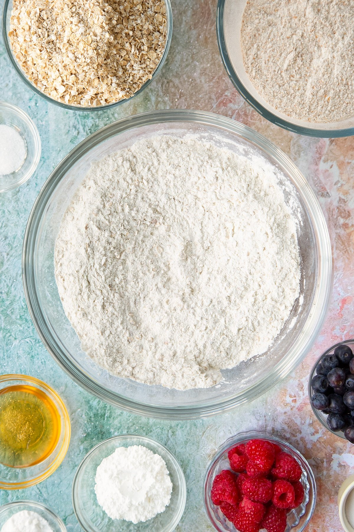 Self-raising flour, bicarbonate of soda, sugar and oats combined in a glass mixing bowl. Ingredients to make oatmeal scones surround the bowl.
