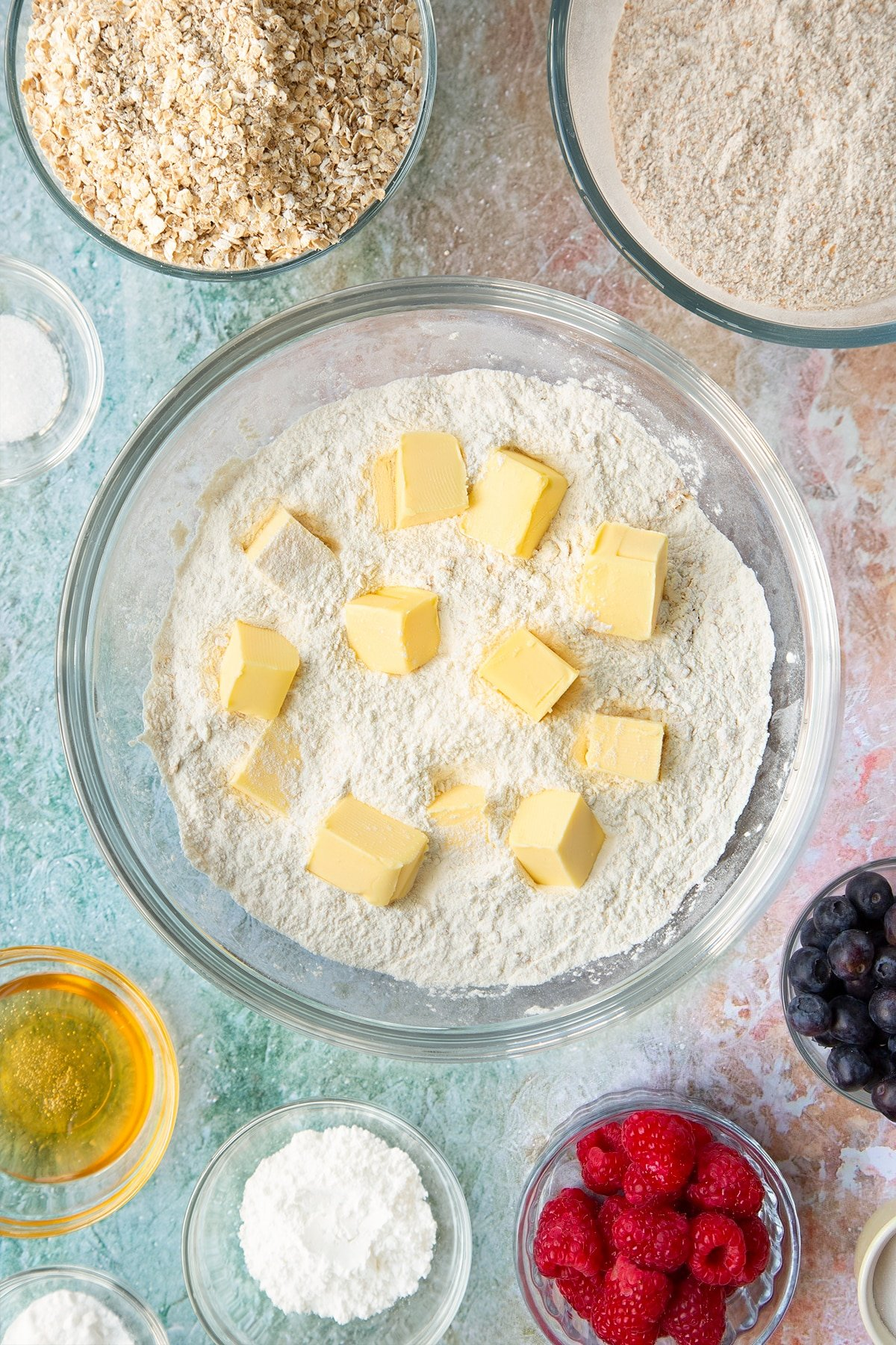 Self-raising flour, bicarbonate of soda, sugar and oats combined in a glass mixing bowl with cubed butter on top. Ingredients to make oatmeal scones surround the bowl.