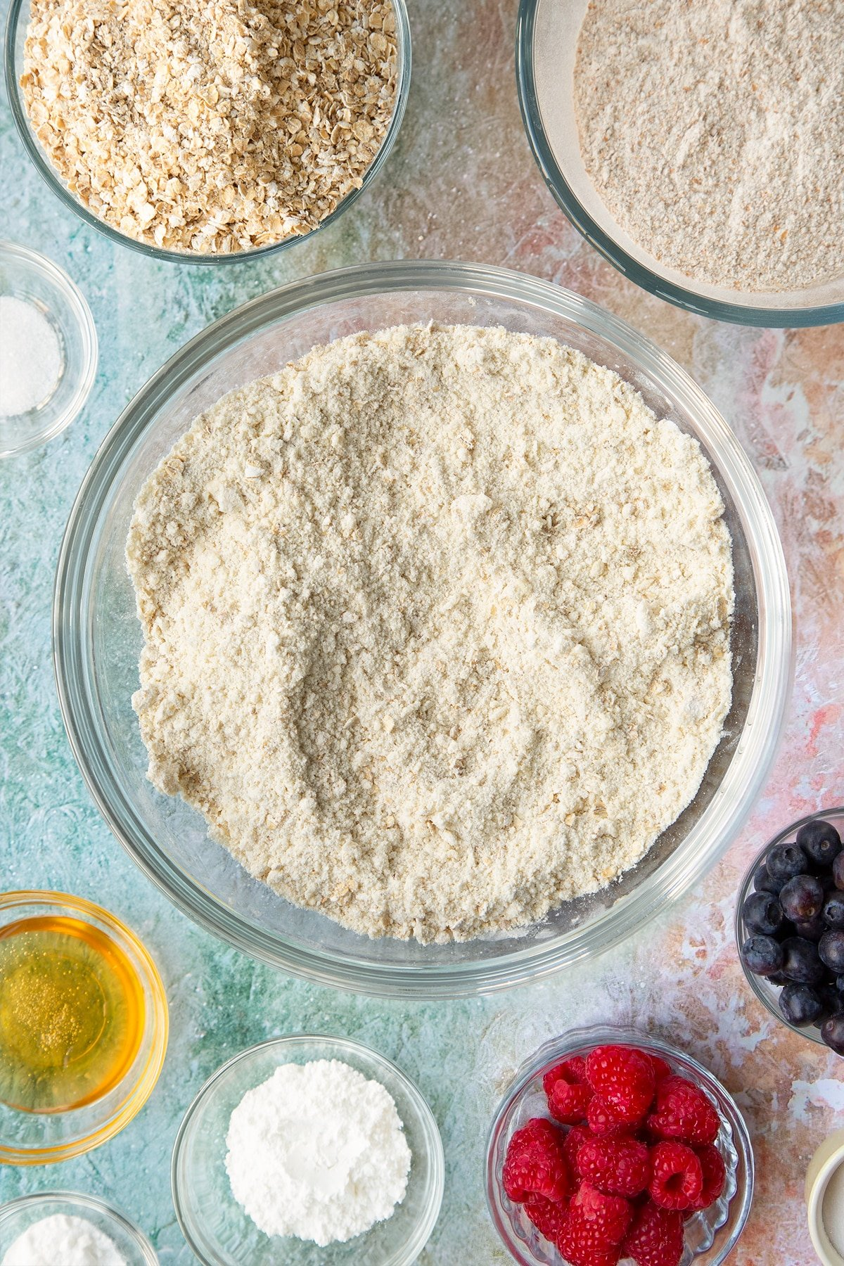 Butter rubbed into self-raising flour, bicarbonate of soda, sugar and oats in a glass mixing bowl. Ingredients to make oatmeal scones surround the bowl.